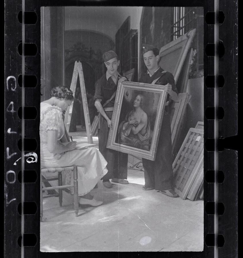 Mulher fazendo inventário de pinturas na coleção do convento de Las Descalzas Reales com dois soldados republicanos , Madrid, outubro - novembro de 1936. Fotografia de Chim (David Seymour)
