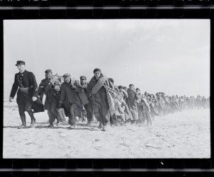 Refugiados andando na praia. Campo de internação francês para exilados republicanos, Le Barcarès, França. Março de 1939. Fotografia de Robert Capa (Fotos: © International Center Of Photography / Magnum Collection International Center of Photography)