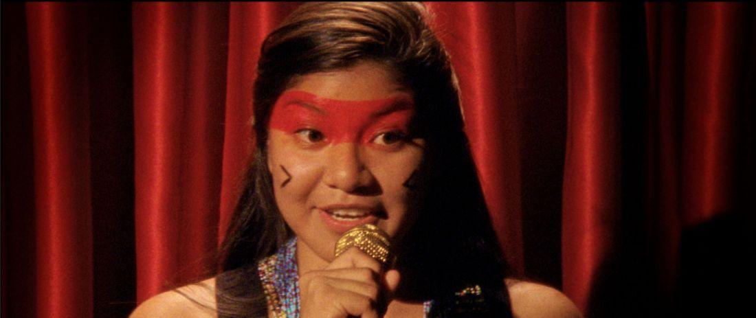 Cena do filme ficcional Joking Relationships, do norte-americano residente em Lisboa Gabriel Abrantes, em que uma índia do Xingu disputa piadas com um robô em stand-up comedy (Foto: Cortesia do artista)